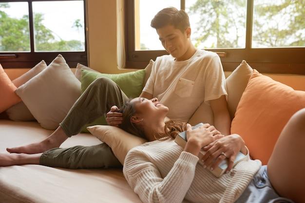 Het jonge paar ontspannen op de bank die thuis van een boek en een bedrijf van elkaar geniet