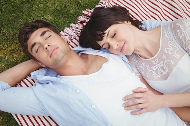 Het jonge paar ontspannen op deken in tuin