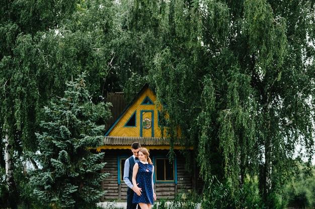 Het jonge paar permanent en knuffelen op de achtergrond een oud houten huis op een eiland