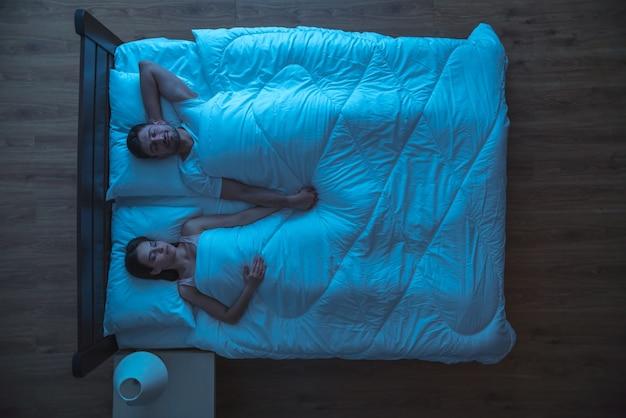 Het jonge paar slaapt op het bed. nacht tijd. uitzicht van boven