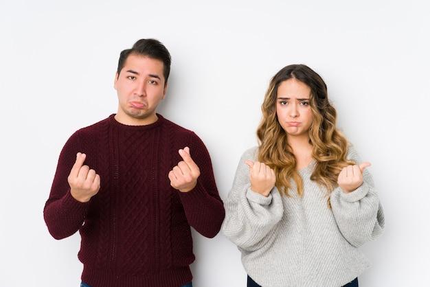 Het jonge paar stellen in een witte muur die aantoont dat zij geen geld heeft.