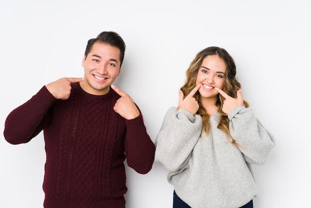Het jonge paar stellen op een witte achtergrond glimlacht, wijzend vingers op mond.