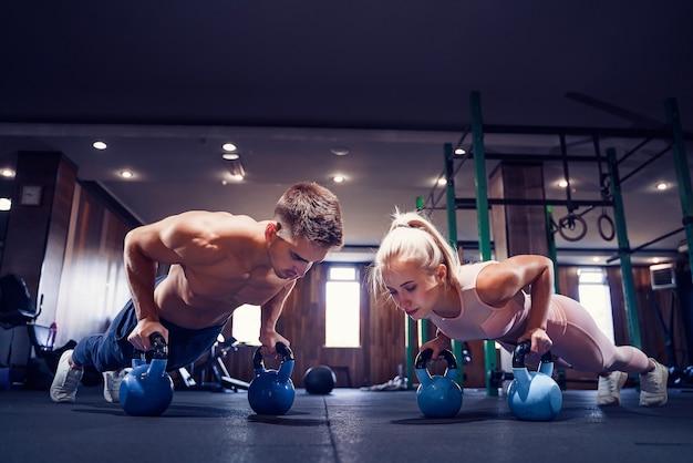 Het jonge paar werkt bij gymnastiek uit. aantrekkelijke vrouw en knappe gespierde man trainen in de moderne sportschool. plank doen op kettlebell. push-up op gewichten.