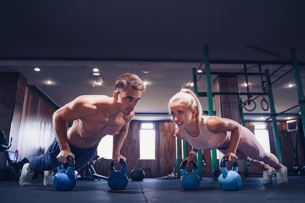 Het jonge paar werkt bij gymnastiek uit. aantrekkelijke vrouw en knappe gespierde man trainen in de moderne sportschool. plank doen op kettlebell. push-up op gewichten. Premium Foto