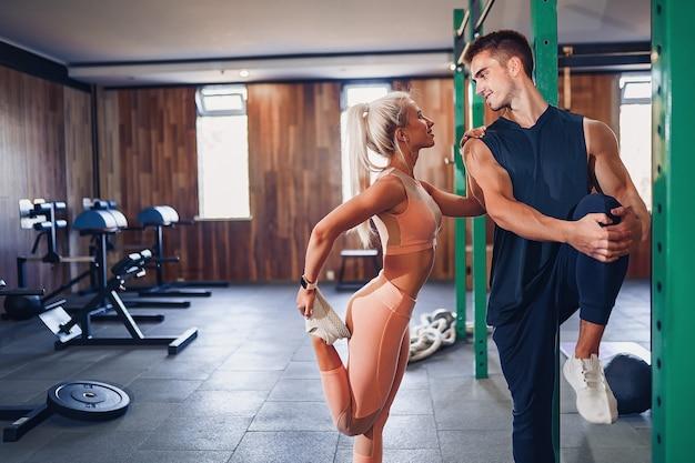 Het jonge paar werkt bij gymnastiek uit. aantrekkelijke vrouw en knappe gespierde man trainen in de moderne sportschool.