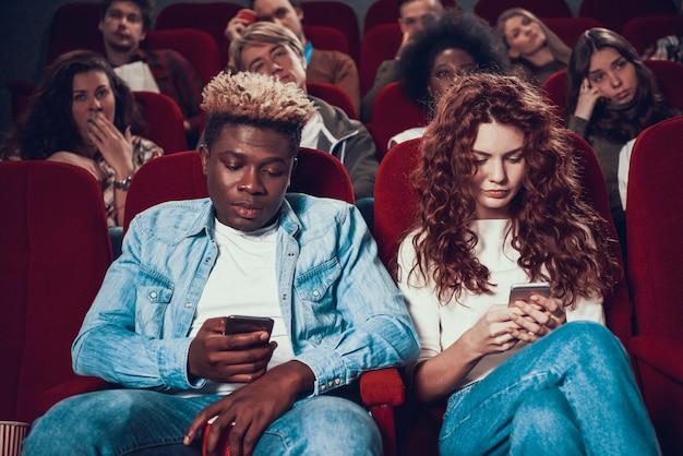 Het jonge paar zit in de bioscoop kijken naar telefoons.
