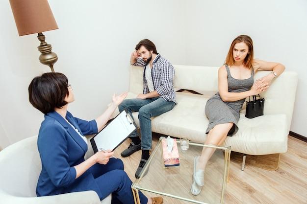 Het jonge paar zit samen en kijkt aan verschillende kanten. ze hebben en argumentatie. psychologis zit voor hen en probeert hen te helpen. ze praat tegen hen