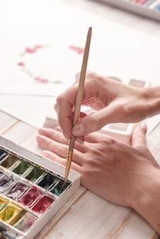 Het jonge patroon van de kunstenaarstekening met waterverfverf en borstel