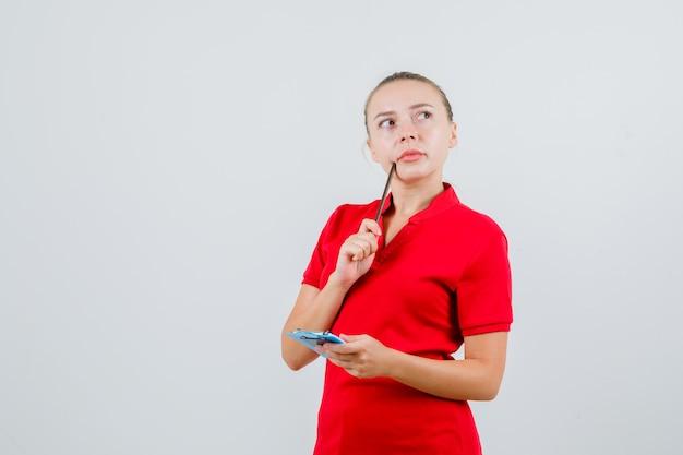 Het jonge potlood en het klembord van de vrouwenholding in rode t-shirt en peinzend kijkt