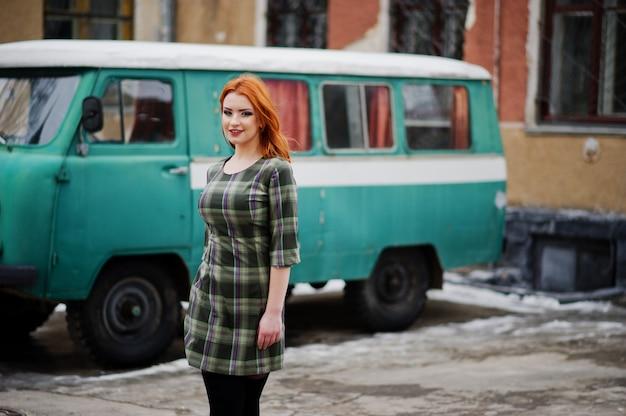 Het jonge rode haired vrouw stellen op geruite kleding in oude retro cyaan minivan.