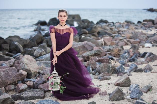 Het jonge romantische vrouw stellen op het strand die op de zonsondergang letten