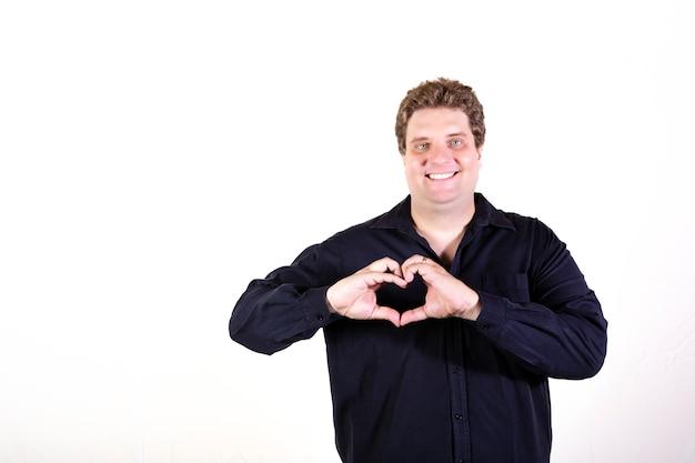 Het jonge ronde mens stellen op het witte muur geïsoleerde glimlachen en het tonen van een hartvorm met handen.