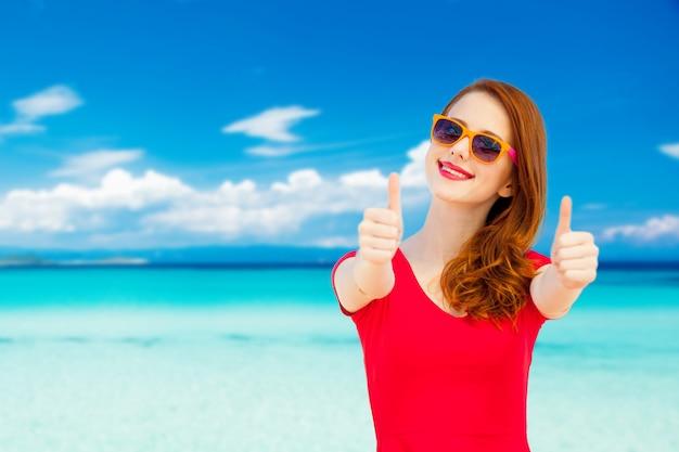 Het jonge roodharige meisje in rode kleding toont ok symbool op zomerstrand