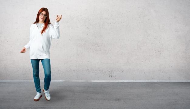 Het jonge roodharigemeisje in een stedelijk wit sweatshirt met glazen geniet van dansend