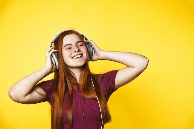 Het jonge roodharigemeisje is gelukkig en het luisteren muziek via hoofdtelefoons met gesloten ogen