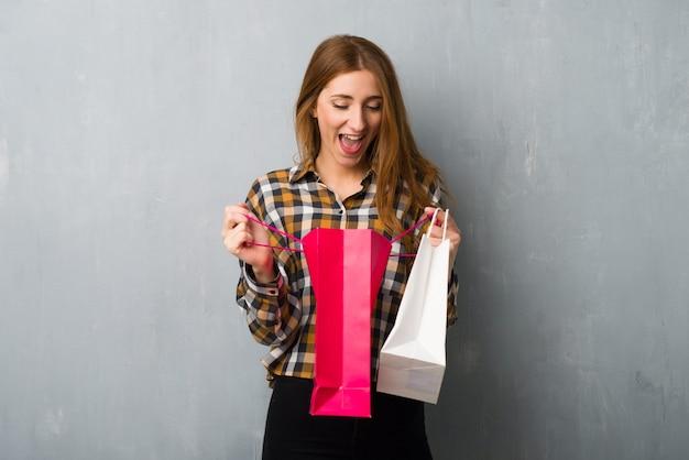 Het jonge roodharigemeisje over grungemuur verraste terwijl het houden van heel wat het winkelen zakken