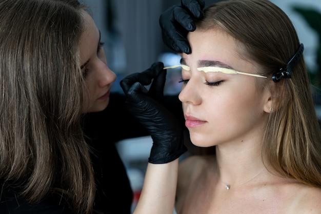 Het jonge schoonheidsspecialist kaukasische meisje houdt modelwenkbrauwcorrectie