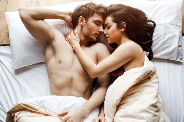 Het jonge sexy paar heeft intimiteit op bed. heel dicht bij elkaar liggen. vrouwelijk model omarmen man. liegen met gesloten ogen. seks in bed. witte kussens. slapen.