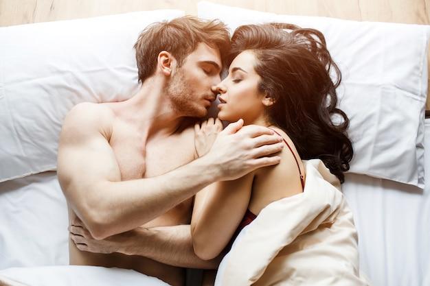 Het jonge sexy paar heeft intimiteit op bed. liggend in slapende houding. omhels elkaar. zoenen hartstochtelijk paar samen in bed. witte achtergrond. daglicht. mooie mensen.