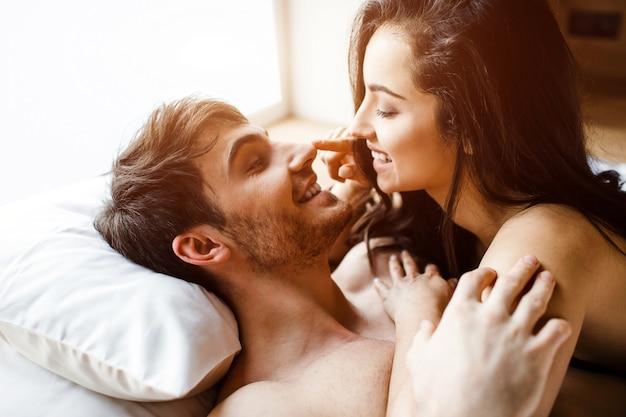 Het jonge sexy paar heeft intimiteit op bed. vrolijke leuke positieve gelukkige mensen glimlachen naar elkaar. ze lag op hem. gelukkige paar samen. daglicht.