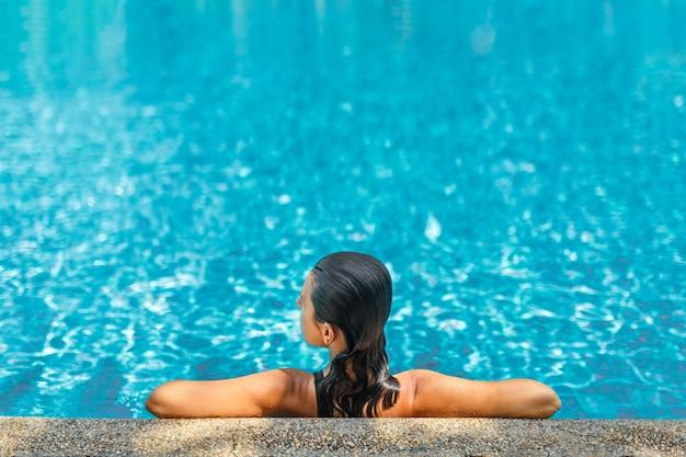 Het jonge sexy slanke vrouw ontspannen in tropisch zwembad met kristalblauw water in hete de zomerdag