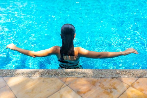 Het jonge sexy slanke vrouw ontspannen in tropisch zwembad met kristalblauw water in hete de zomerdag.