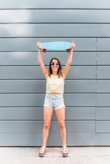 Het jonge skateboard van de vrouwenholding boven hoofd