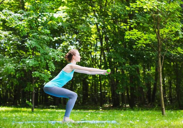 Het jonge slanke meisje doet oefeningen in openlucht.