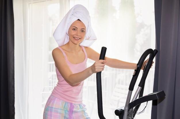 Het jonge slanke meisje gaat thuis sporten binnen. een conceptuele foto over de voordelen van sport en een gezonde levensstijl.