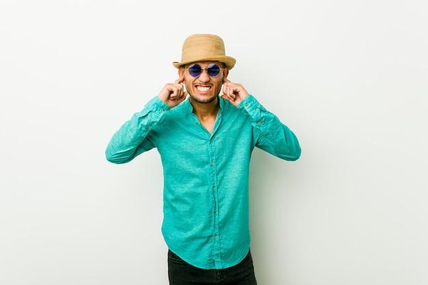 Het jonge spaanse mens dragen de zomerkleren die oren behandelen met handen.