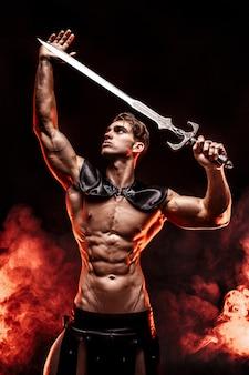 Het jonge spiermodel stellen met zwaard in handen en weg het kijken