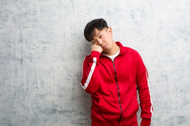 Het jonge sportfitness chinese denken aan iets, kijkend aan de kant