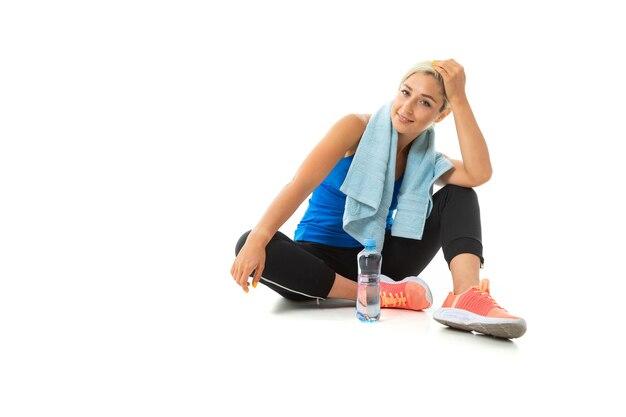 Het jonge sportieve meisje met blond haar ontspant na geïsoleerde opleiding