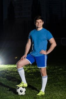 Het jonge sportman stellen dichtbij voetbalbal