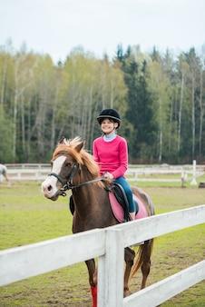 Het jonge sportvrouw het berijden paard in ruiter toont de sprongenconcurrentie. tiener rijdt op een paard
