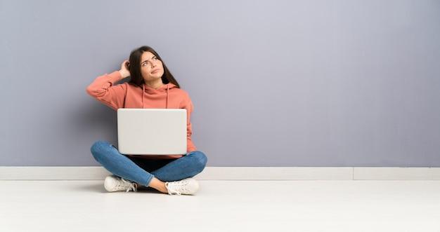 Het jonge studentenmeisje met laptop op de vloer die twijfels hebben en verwart gezichtsuitdrukking