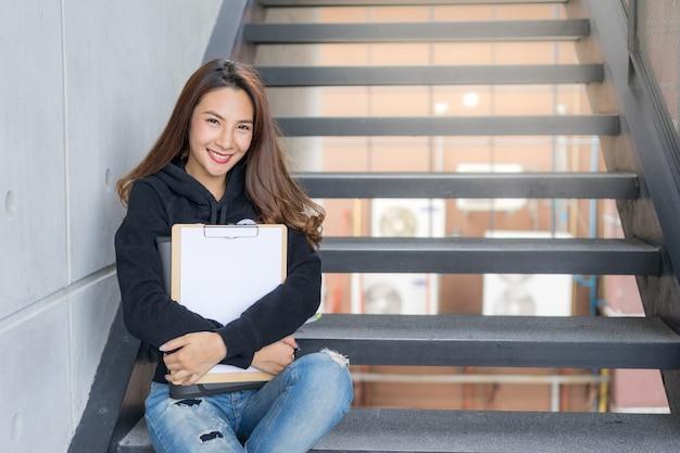Het jonge studentenwijfje zit op treden met de omslag en het copy-book op campusgebied