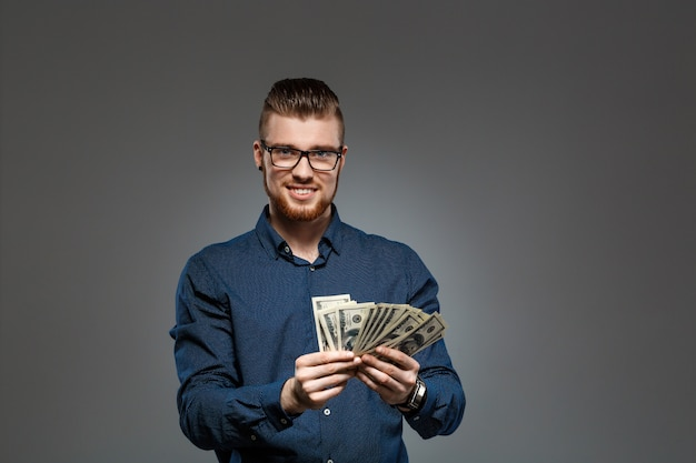 Het jonge succesvolle geld van de zakenmanholding over donkere muur.
