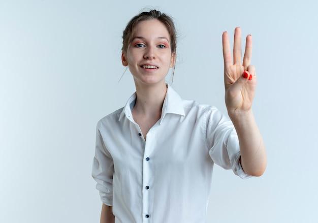 Het jonge tevreden blonde russische meisje gebaart drie met vingers die op witte ruimte met exemplaarruimte worden geïsoleerd
