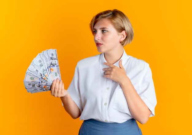 Het jonge tevreden blonde russische meisje houdt geld bekijkt die kant op oranje achtergrond met exemplaarruimte wordt geïsoleerd