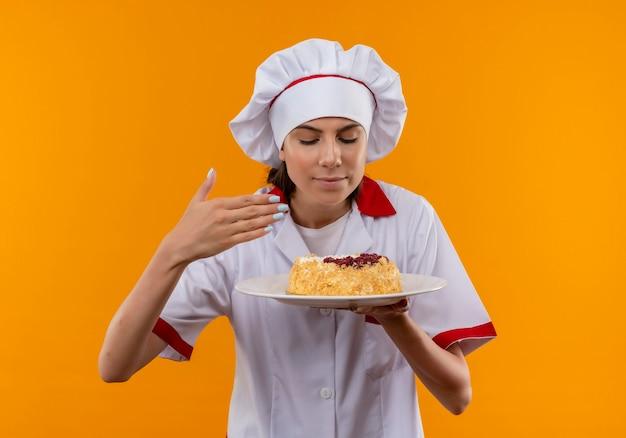 Het jonge tevreden kaukasische kokmeisje in eenvormige chef-kok houdt en beweert cake op plaat te ruiken die op oranje achtergrond met exemplaarruimte wordt geïsoleerd
