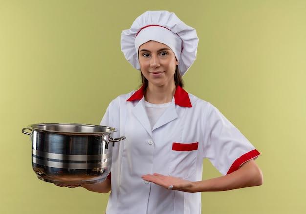 Het jonge tevreden kaukasische kokmeisje in eenvormige chef-kok houdt en wijst op pot die op groene achtergrond met exemplaarruimte wordt geïsoleerd