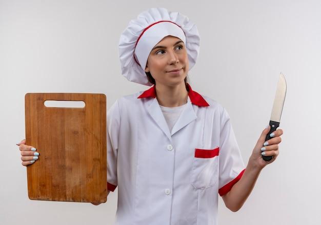 Het jonge tevreden kaukasische kokmeisje in eenvormige chef-kok houdt mes en scherpe raad op wit met exemplaarruimte