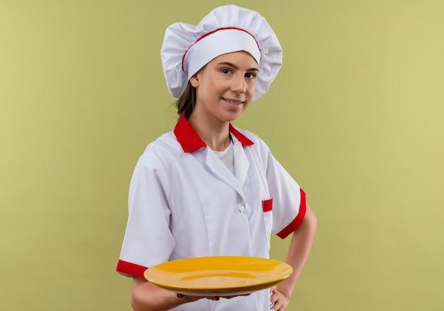 Het jonge tevreden kaukasische kokmeisje in eenvormige chef-kok houdt plaat en legt hand op taille op groen met exemplaarruimte