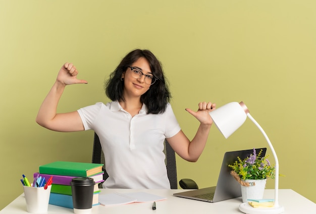 Het jonge tevreden vrij kaukasische schoolmeisje die glazen dragen zit aan bureau met de punten van schoolhulpmiddelen op zichzelf geïsoleerd op groene ruimte met exemplaarruimte