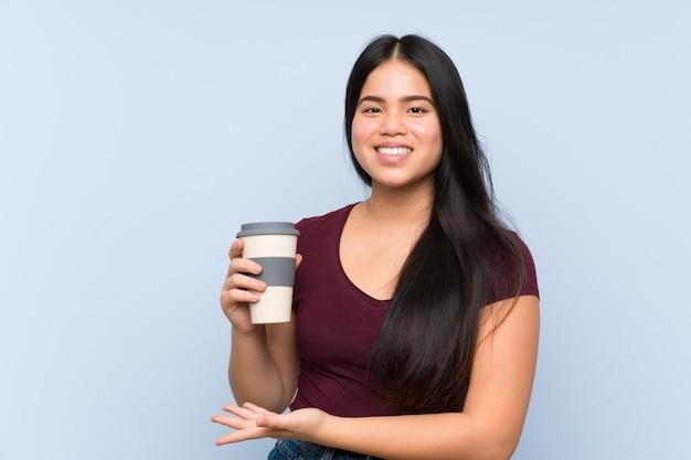 Het jonge tiener aziatische meisje houdt haalt koffie weg
