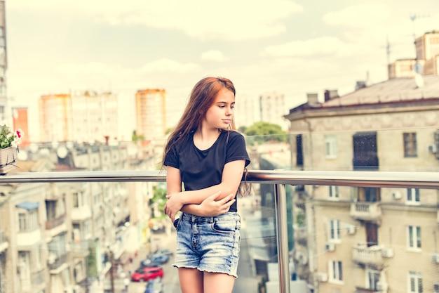 Het jonge tiener donkerbruine model stellen. een kind in de stad. meisje 10 jaar oud