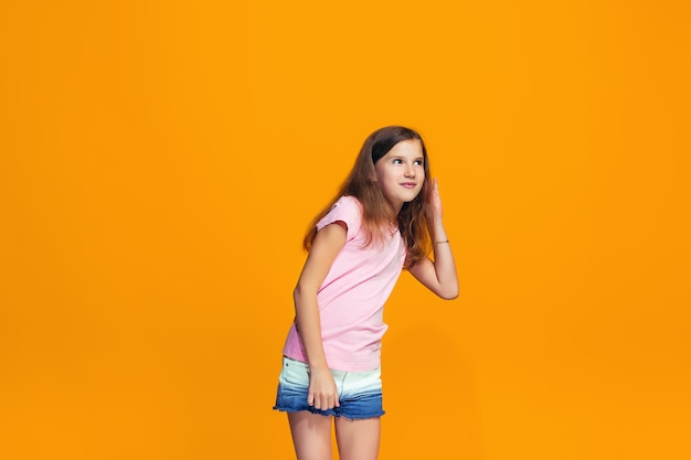 Het jonge tienermeisje dat een geheim achter haar fluistert overhandigt oranje ruimte