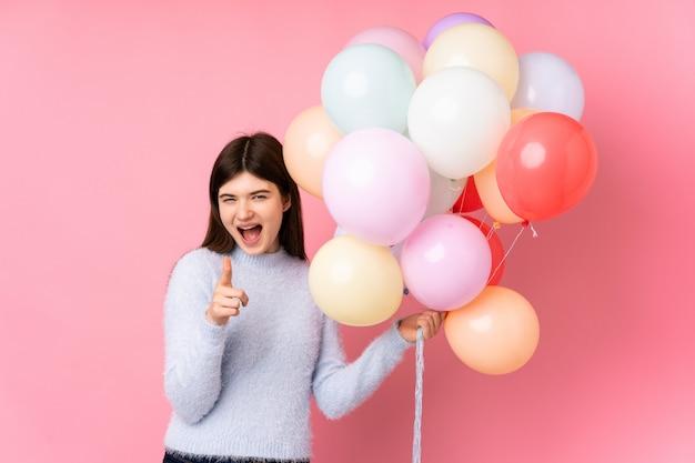 Het jonge tienermeisje dat veel ballons over roze muur houdt richt vinger op u