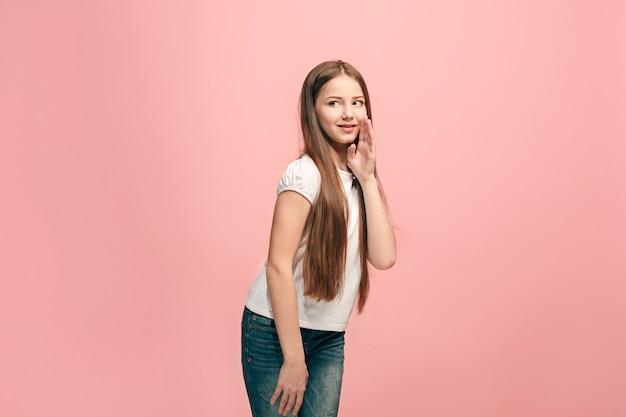 Het jonge tienermeisje fluistert een geheim achter haar hand over roze muur